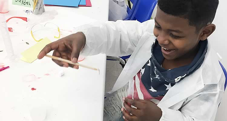 Boy painting at Elmcor's activities event