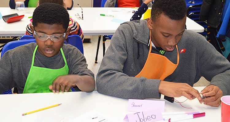 Two young boys in a lab class at Elmcor practicing working with electronics.