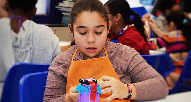 A young girl is focused on her craft at Elmcor Youth and Adult Activities in Queens, New York
